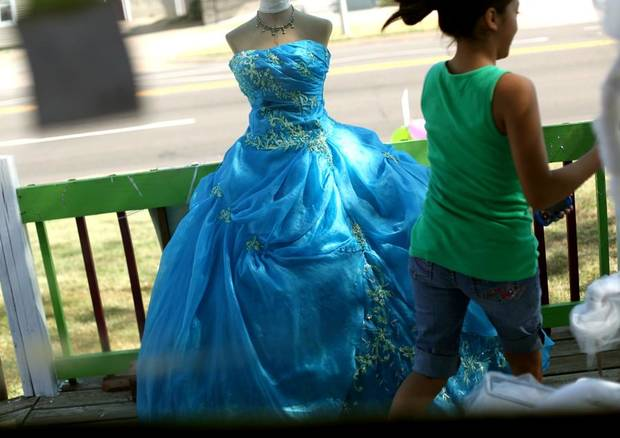DRESS SHOP / STORE: Children walk past a dress that Maria Ramirez made for her daughter, now on display on the front porch at Creaciones Princesa on Friday, August 6,  2010. Photo by John Clanton, The Oklahoman ORG XMIT: KOD