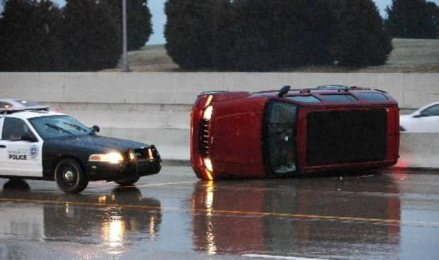 A vehicle sits on its side against the barricade in the median of the southbound lanes of the Broadway Extension at the Wilshire Blvd. exit as storms move through the metro in Oklahoma City Monday, Feb. 25, 2013. Photo by Paul B. Southerland