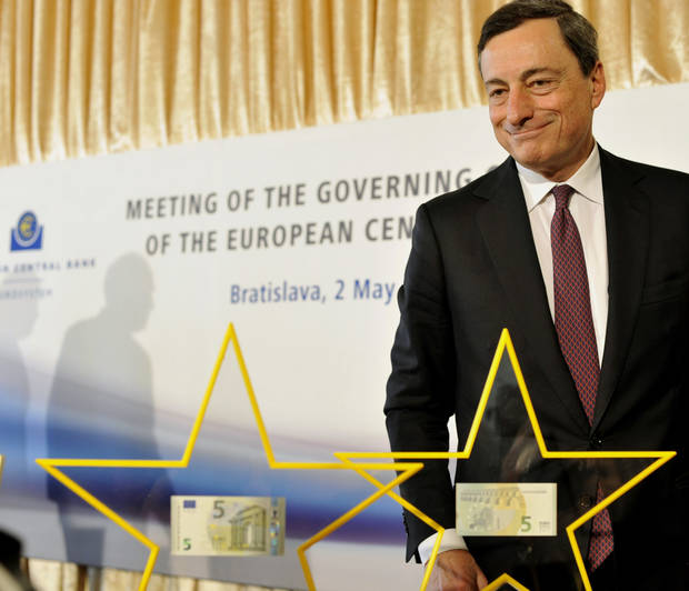 European Central Bank's President Mario Draghi presents a new five euro note at the press conference during the Meeting of the Governing Council of the Eropean Central Bank in Bratislava, Slovakia, Thursday, May 2, 2013. (AP Photo/CTK, Jan Koller) SLOVAKIA OUT