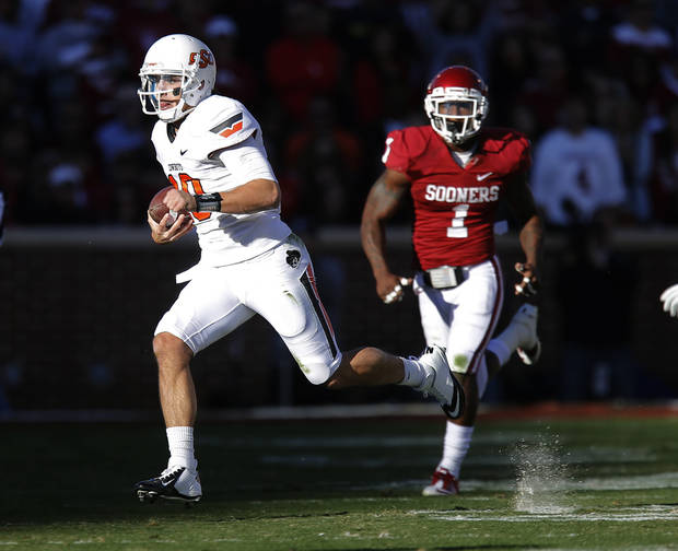 Oklahoma State's Clint Chelf (10) runs past Oklahoma's Tony Jefferson (1) during the Bedlam college football game between the University of Oklahoma Sooners (OU) and the Oklahoma State University Cowboys (OSU) at Gaylord Family-Oklahoma Memorial Stadium in Norman, Okla., Saturday, Nov. 24, 2012. Oklahoma won 51-48. Photo by Bryan Terry, The Oklahoman
