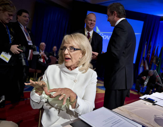 Arizona Gov. Jan Brewer, left, gestures asIshe speaks to a reporter before the start of a Health and Homeland Security Committee meeting on �Protecting Our Nation: States and Cybersecurity� during the National Governors Association 2013 Winter Meeting in Washington, Saturday, Feb. 23, 2013. Standing at the back right, is Governor of Puerto Rico Alejandro García Padilla. Washington's protracted budget stalemate could seriously undermine the economy and stall gains made since the recession, exasperated governors said Saturday as they try to gauge the fallout from impending federal spending cuts. And both Democrat and Republican CEOs expressed pessimism that both sides could find a way to avoid the massive, automatic spending cuts set to begin March 1.   (AP Photo/Manuel Balce Ceneta)