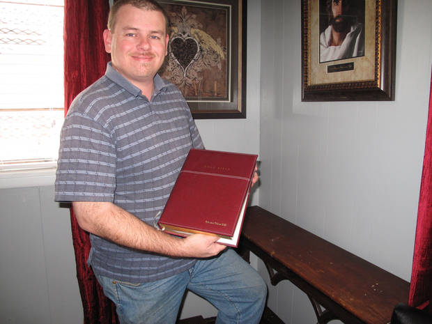 Rick Denny, executive director of the Jesus House, holds a new engraved Bible presented to the emergency shelter by friends and family of Braylee Rae Henry. <strong>CARLA HINTON - CARLA HINTON</strong>