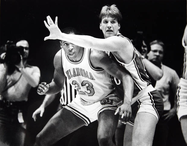 Former OU basketball player Wayman Tisdale. Wayman Tisdale peeks under the arm of Paul Brozovich, one of three Rebels who fouled out. 3-4-84 ORG XMIT: KOD
