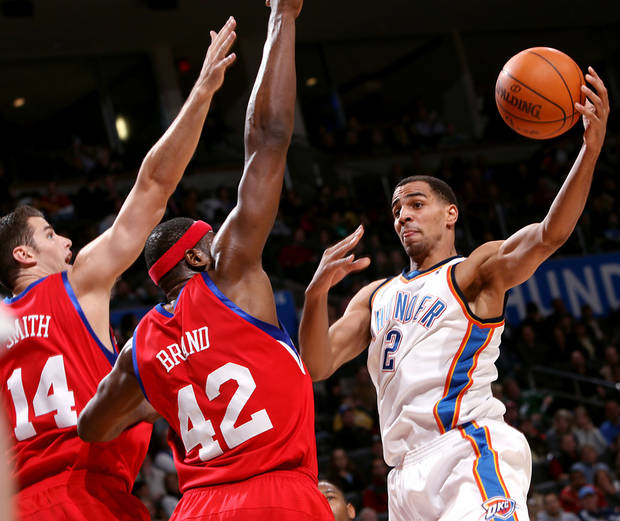 Oklahoma City's Thabo Sefolosha looks for an open teammate against pressure from Philadelphia's Jason Smith and Elton Brand during the first half of their NBA basketball game at the Ford Center in Oklahoma City on Tuesday, Dec. 2, 2009. By John Clanton, The Oklahoman