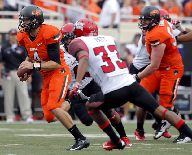 Oklahoma State's J.W. Walsh (4)  scrambles as Louisiana-Lafayette's Trevence Patt (33) chases him down  during a college football game between Oklahoma State University (OSU) and the University of Louisiana-Lafayette (ULL) at Boone Pickens Stadium in Stillwater, Okla., Saturday, Sept. 15, 2012. Photo by Sarah Phipps, The Oklahoman
