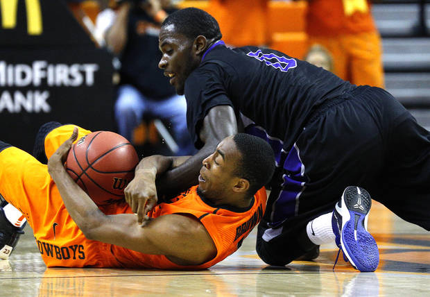 Oklahoma State's Markel Brown (22) and Central Arkansas' Robert Crawford (0) fight for a loose ball during the men's college basketball game between Oklahoma State University and Central Arkansas at Gallagher-Iba Arena in Stillwater, Okla., Sunday,Dec. 16, 2012. Photo by Sarah Phipps, The Oklahoman