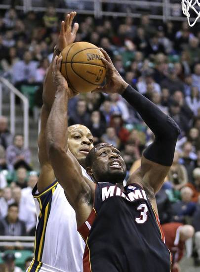 Miami Heat guard Dwyane Wade (3) goes to the basket as Utah Jazz  guard Randy Foye (8) defends in the first quarter of an NBA basketball game Monday, Jan. 14, 2013, in Salt Lake City.  (AP Photo/Rick Bowmer)