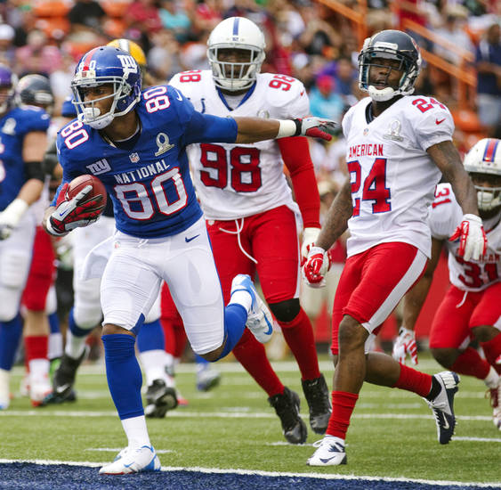 New York Giants wide receiver Victor Cruz (80) of the NFC breaks away from Indianapolis Colts outside linebacker Robert Mathis (98) and Houston Texans cornerback Johnathan Joseph (24) of the AFC to score a touchdown in the second quarter of the NFL football Pro Bowl game in Honolulu, Sunday, Jan. 27, 2013. (AP Photo/Eugene Tanner)