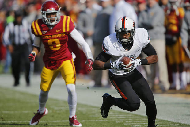 Oklahoma State 's Justin Gilbert (4) makes an interception for a touchdown in front of Iowa State's Quenton Bundrage (9) during the college football game between the Oklahoma State University Cowboys (OSU) and the Iowa State University Cyclones (ISU) at Jack Trice Stadium in Ames, Iowa, on Saturday, Oct. 26, 2013.  Photo by Chris Landsberger, The Oklahoman