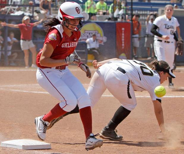 Oklahoma's Destinee Martinez (00) makes it to first as the ball goes past Missouri's Ashley Fleming (30) in the seventh inning of a Women's College World Series softball game between the University Oklahoma and Missouri at ASA Hall of Fame Stadium in Oklahoma City, Saturday, June 4, 2011. Missorui won, 4-1. Photo by Bryan Terry, The Oklahoman