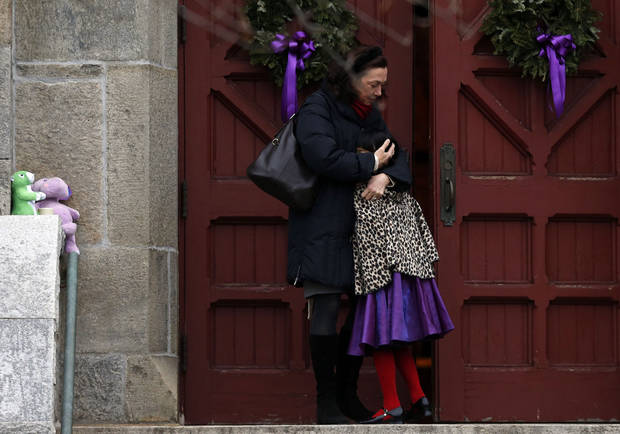 A woman hugs a young girl as they arrive for services at Trinity Church, Sunday, Dec. 16, 2012 in Newtown, Conn.  A gunman walked into Sandy Hook Elementary School in Newtown Friday and opened fire, killing 26 people, including 20 children. (AP Photo/Jason DeCrow)