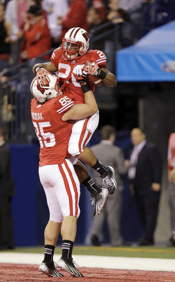 Wisconsin running back James White (20) celebrates with Brian Wozniak after White ran 68 yards for a touchdown during the second half of the Big Ten Conference championship NCAA college football game against Nebraska Saturday, Dec. 1, 2012, in Indianapolis. (AP Photo/Michael Conroy)
