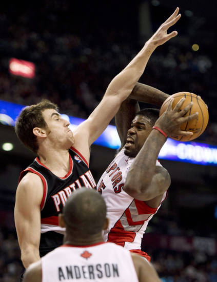 Toronto Raptors forward Amir Johnson, right, runs into defense from Portland Trail Blazers forward Victor Claver during the first half of an NBA basketball game in Toronto, Wednesday, Jan. 2, 2013. (AP Photo/The Canadian Press, Frank Gunn)