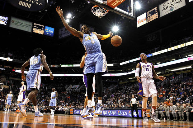 Denver Nuggets' Andre Iguodala (9) reacts after dunking the ball as Phoenix Suns' Michael Beasley (0) watches during the first half of an NBA basketball game, Monday, Nov. 12, 2012, in Phoenix. (AP Photo/Ross D. Franklin)