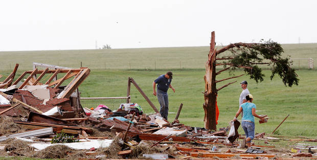 Kiley Witte, 34, left, is joined by two friends walking the rubble of his home on SH 74 east of Cashion after a tornado destroyed it  Tuesday afternoon,  May 24, 2011,   Witte and his dog were in a storm cellar in his front yard.  His wife and young son had done to Oklahoma City and were in a safe room of a business where she works.  Photo by Jim Beckel, The Oklahoman
