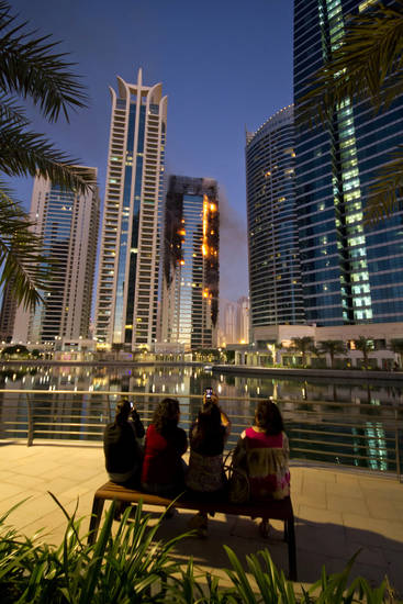 A woman takes photo of Tamweel residential tower as flames engulf a portion of the building at Jumeirah Lakes Towers, in Dubai, United Arab Emirates, Sunday, Nov. 18, 2012. Civil defense officials did not give immediate details on possible casualties or the cause of the predawn fire. (AP Photo/Kaveh Kashani)