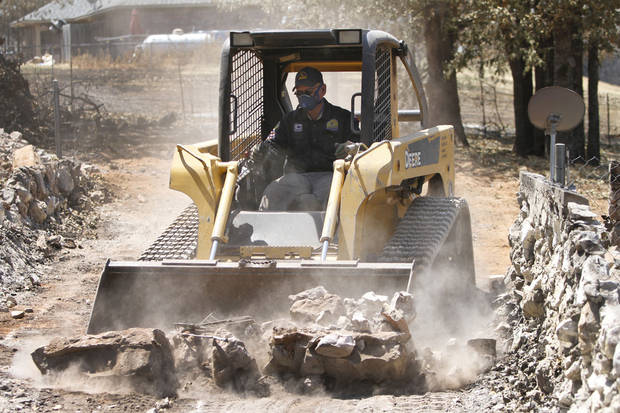 Southern Baptist Convention volunteer Jim Howard on Monday uses a front end loader to remove rubble from a home that was destroyed in a wildfire on 130th Street in Noble.  Photo By Steve Gooch, The Oklahoman <strong>Steve Gooch</strong>