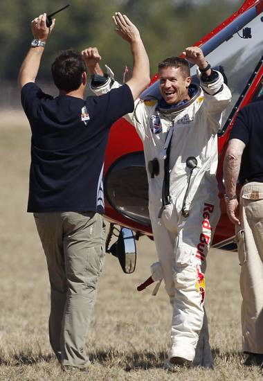 Felix Baumgartner, right, of Austria, celebrates with Luke Aikins, team skydiving consultant, after Baumgartner successfully jumped from a space capsule lifted by a helium balloon at a height of just over 128,000 feet above the Earth's surface, Sunday, Oct. 14, 2012, in Roswell, N.M.(AP Photo/Ross D. Franklin) ORG XMIT: NMRF123