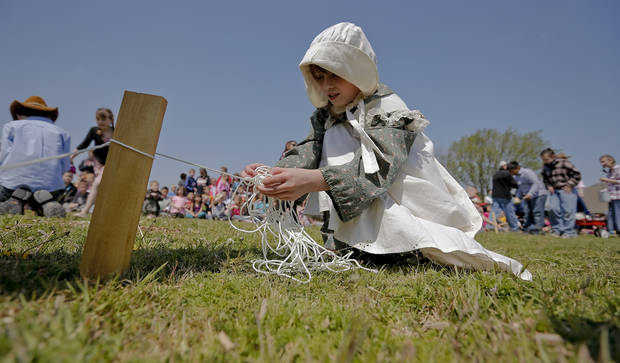 Kyndal Jackson ties to get the knot of the string so she can rope off her claim of land during the Oklahoma Land Run celebration at Mustang Trails Elementary on Monday, April 22, 2013, in Mustang, Okla.   Photo by Chris Landsberger, The Oklahoman