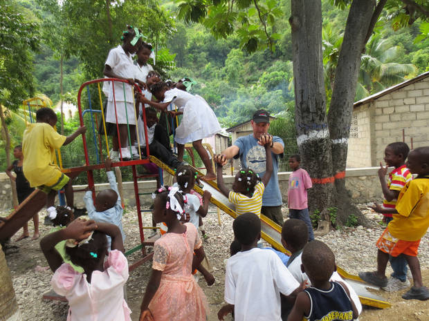 Randy Decker, director of community relations for SandRidge Energy, plays with children in Frettas, Haiti, in November. It was Decker's second volunteer trip to the impoverished island nation. <strong> - Provided</strong>