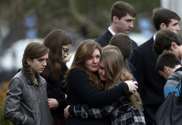 Mourners comfort one another as they leave a funeral service for 6-year-old Noah Pozner, Monday, Dec. 17, 2012, in Fairfield, Conn.  Pozner was killed when a gunman walked into Sandy Hook Elementary School in Newtown Friday and opened fire, killing 26 people, including 20 children. (AP Photo/Jason DeCrow)
