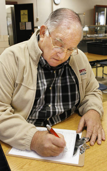 John Smith fills out a form Wednesday to get a flu shot at Mark Twain Elementary School. Photo by Paul B. Southerland, The Oklahoman <strong>PAUL B. SOUTHERLAND</strong>