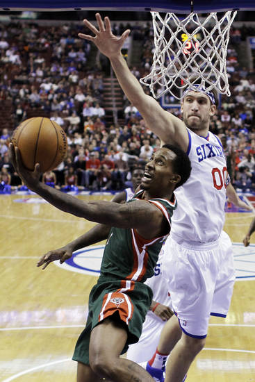Milwaukee Bucks' Brandon Jennings, left, goes up for a shot past Philadelphia 76ers' Spencer Hawes in the first half of an NBA basketball game, Monday, Nov. 12, 2012, in Philadelphia. (AP Photo/Matt Slocum)