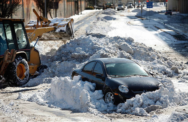 A front-end loader removes snow around an abandonded car on E.K. Gaylord and Robert S. Kerr. Many spent Christmas Day, Dec. 25, 2009,  digging out from record snow storm that dumped 14 inches of snow in the Oklahoma City area.   Photo by Jim Beckel, The Oklahoman