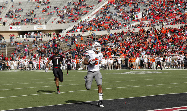 Oklahoma State Cowboys wide receiver Josh Stewart (5) scores a touchdown in front of Texas Tech Red Raiders safety Terrance Bullitt (1) during the college football game between the Oklahoma State University Cowboys (OSU) and Texas Tech University Red Raiders (TTU) at Jones AT&T Stadium on Saturday, Nov. 12, 2011. in Lubbock, Texas.  Photo by Chris Landsberger, The Oklahoman  ORG XMIT: KOD