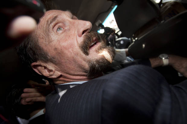 Software company founder John McAfee is surrounded by members of the press as he leaves an immigration detention center for the La Aurora international airport in Guatemala City, Wednesday Dec. 12, 2012. McAfee, who is being deported to the U.S., was detained last week for immigration violations after he sneaked into Guatemala from neighboring Belize, where authorities sought to question him about the murder of his neighbor. (AP Photo/Moises Castillo)