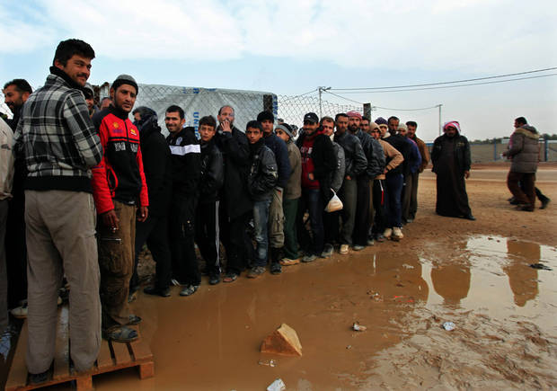 Newly arrived Syrian refugees wait their turn to receive mattresses, blankets and other supplies, and to be assigned to tents, at the Zaatari Syrian refugees camp in Mafraq, near the Syrian border with Jordan, Monday, Jan. 28, 2013.  UN officials say a spike in Syrian refugees fleeing to Jordan in the past week has seen about 21,000 new arrivals with Jordan�s Zaatari refugee camp now hosting about 83,000 registered refugees.  (AP Photo/Mohammad Hannon)
