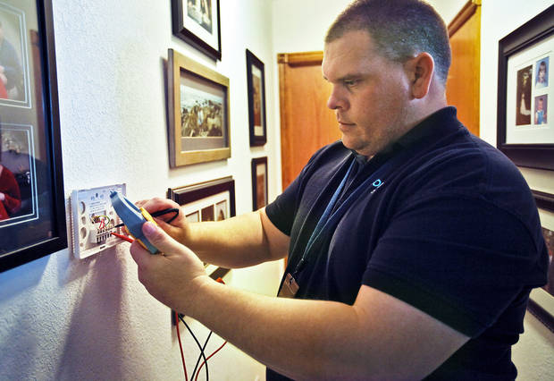 Oklahoma Gas and Electric Co. worker Greg Henderson installs a new programmable thermostat Thursday at a house in Piedmont. The thermostat can communicate with a smart meter at the house to help reduce electricity costs.  Photos by Chris Landsberger, The Oklahoman
