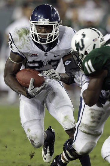 University of Connecticut running back Jordan Todman (23) makes a move on South Florida linebacker Sabbath Joseph (11) during the fourth quarter of an NCAA college football game Saturday, Dec. 4, 2010, in Tampa, Fla. (AP Photo/Chris O'Meara) ORG XMIT: TPS112