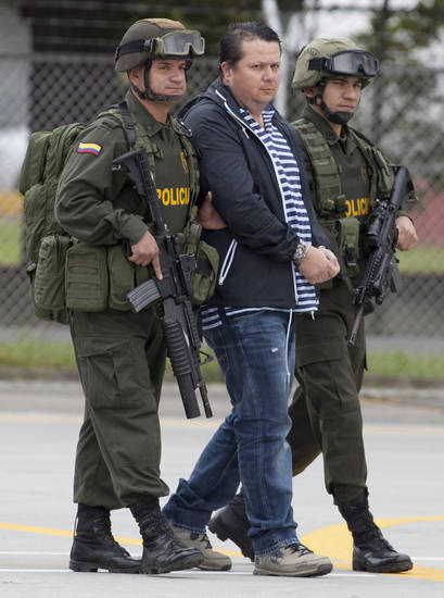 Police officers escort Costa Rican Alejandro Jimenez Gonzalez to a police station in Bogota, Colombia, Tuesday March 13, 2012. Jimenez is suspected of ordering the attack that resulted in the murder of Argentine folk singer Facundo Cabral, who was gunned down last year in an ambush in Guatemala. Authorities believe the attack was aimed at the Nicaraguan businessman who was driving the singer to the airport. That man was wounded. (AP Photo/Fernando Vergara)