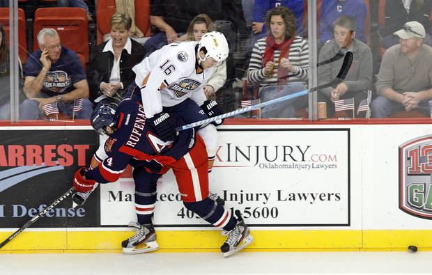 Grand Rapids' Bryan Rufenach (44) checks Oklahoma City's Magnus Paajarvi (16) into the boards during an AHL hockey game between the Oklahoma City Barons and the Grand Rapids Griffins at the Cox Convention Center in Oklahoma City, Saturday, March 24, 2012. Photo by Nate Billings, The Oklahoman