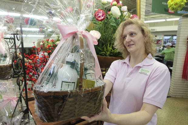 Georgianna Gleason shows a Valentine's Day gift basket at Trocta's Flowers & Greenhouses, one of several retailers coping with a helium shortage. <strong>David McDaniel - The Oklahoman</strong>