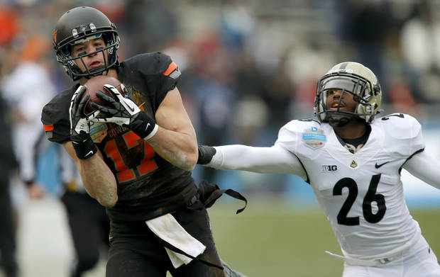 Oklahoma State's Charlie Moore (17) catches a pass in front of Purdue's Antoine Lewis (26) during the Heart of Dallas Bowl football game between Oklahoma State University and Purdue University at the Cotton Bowl in Dallas, Tuesday, Jan. 1, 2013. Oklahoma State won 58-14. Photo by Bryan Terry, The Oklahoman