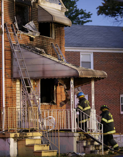 Officials walk into a fire-damaged house in Baltimore, where an early morning fire claimed the lives of an adult and four children Thursday, Oct. 11, 2012. (AP Photo/Patrick Semansky)