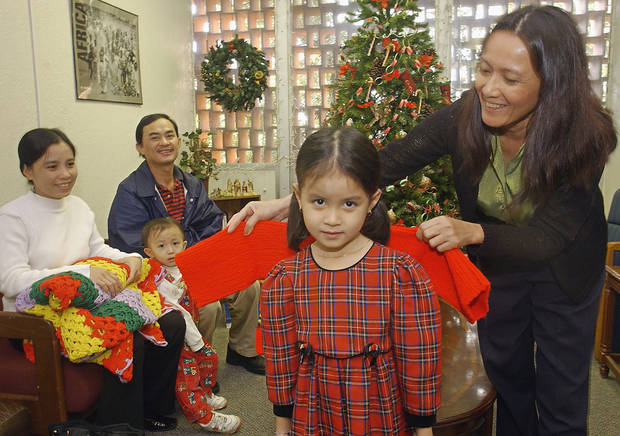 In this 2003 photo, Catholic Charities case manager Tina Loan Nguyen holds up a sweater to see if it fits Trinh Trung Hoang at the Catholic Charities  office. <strong>David McDaniel</strong>