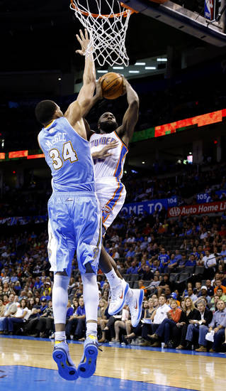 Oklahoma City's James Harden (13) dunks over Denver's JaVale McGee (34) during the NBA preseason basketball game between the Oklahoma City Thunder and the Denver Nuggets at the Chesapeake Energy Arena, Sunday, Oct. 21, 2012. Photo by Sarah Phipps, The Oklahoman