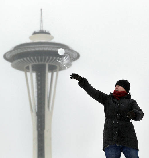 FILE - In this Jan. 18, 2012 file photo, the the Space Needle is shown in the background as Lynne Wyllie tosses a snowball in a downtown Seattle park. With 2013's winter half-over and mild weather holding for Seattle, the city could make it through the season without a significant snowfall. Meteorologist Johnny Burg said said Monday, Feb. 11, 2013, that Seattle typically goes without winter snow only once or twice a decade.  (AP Photo/Elaine Thompson, File)