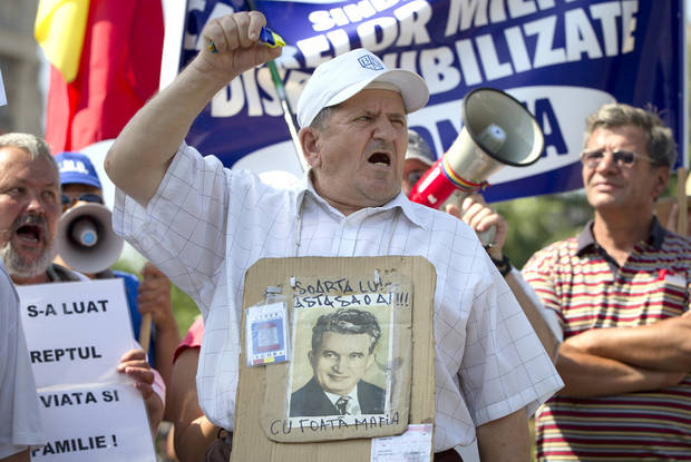 "A protester holding a poster depicting communist dictator Nicolae Ceausescu shouts during a rally calling for the impeachment of Romania's president Traian Basescu, attended by military pensioners in Bucharest, Romania, Saturday, July 14, 2012. Basescu was suspended by parliament and will face a referendum on impeachment on July 29, 2012. Poster reads ""You should face his fate""(AP Photo/Vadim Ghirda)"