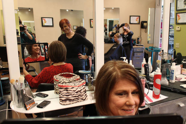 Lynn Bunting looks at the back of her hair after having a haircut by Savannah Jenkins, who looks on. Photo by Heather Warlick, The Oklahoman. <strong></strong>