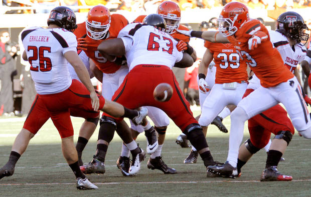 Oklahoma State's Zack Craig (23) blocks a punt by Texas Tech's Ryan Erxleben (26) during the college football game between the Oklahoma State University Cowboys (OSU) and Texas Tech University Red Raiders (TTU) at Boone Pickens Stadium on Saturday, Nov. 17, 2012, in Stillwater, Okla.   Photo by Chris Landsberger, The Oklahoman