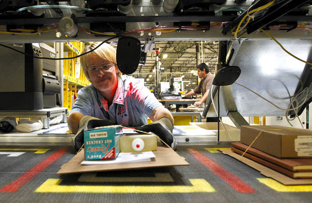 Yolanda Holden places a completed order onto a conveyor belt prior to packaging at the Amazon.com 1.2 million square foot fulfillment center Monday, Nov. 26, 2012, in Phoenix. Americans clicked away on their computers and smartphones for deals on Cyber Monday, which is expected to be the biggest online shopping day in history. Shoppers are expected to spend $1.5 billion on Cyber Monday, up 20 percent from last year, according to research firm comScore. That would not only make it the biggest online shopping day of the year, but the biggest since comScore started tracking shoppers' online buying habits in 2001. (AP Photo/Ross D. Franklin) ORG XMIT: AZRF105