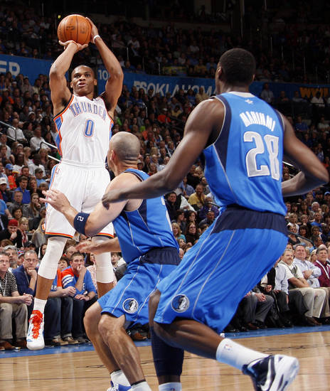 Oklahoma City's Russell Westbook (0) takes a shot as Dallas' Jason Kidd (2) and Ian Mahinmi (28) defend during the NBA basketball game between the Oklahoma City Thunder and the Dallas Mavericks at Chesapeake Energy Arena in Oklahoma City, Monday, March 5, 2012. Photo by Nate Billings, The Oklahoman