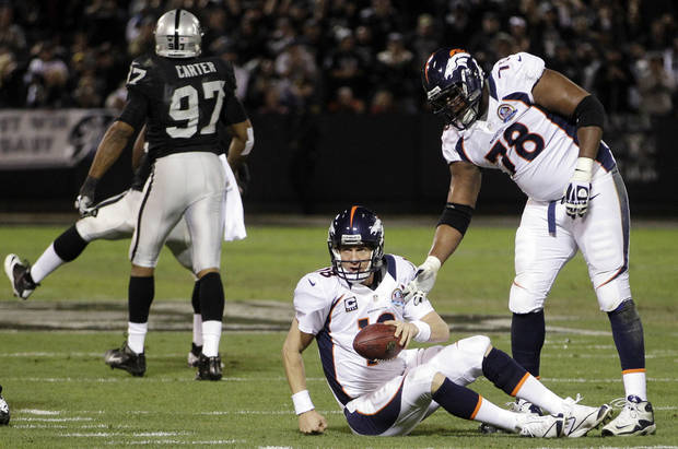 Denver Broncos quarterback Peyton Manning (18) is helped up by tackle Ryan Clady (78) after being sacked during the first quarter of an NFL football game against the Oakland Raiders in Oakland, Calif., Thursday, Dec. 6, 2012. At left is Raiders defensive end Andre Carter (97). (AP Photo/Ben Margot)
