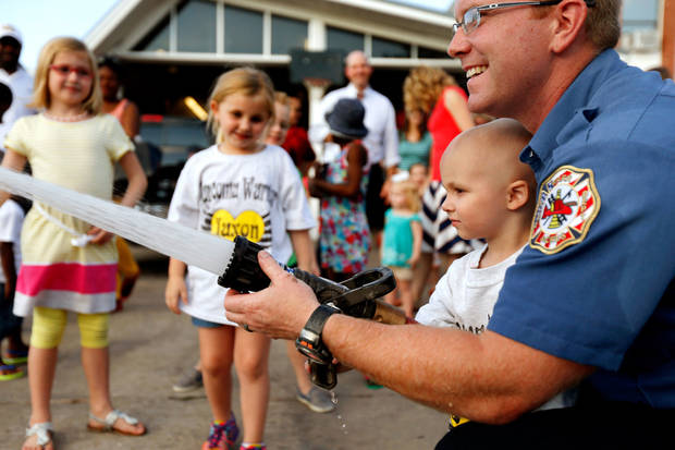 Jaxon Dugger, 3, from Hollis, Okla., gets help from firefighter Clay Carpenter with a fire hose. Photo by Bryan Terry, The Oklahoman