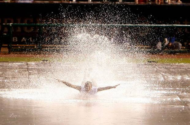 Darren Ransley slides on the tarp during a rain delay of the Oklahoma City RedHawks and Omaha Royals at the At&T Bricktown Ballpark, Saturday July 4, 2009, in Oklahoma City. Photo by Sarah Phipps, The Oklahoman