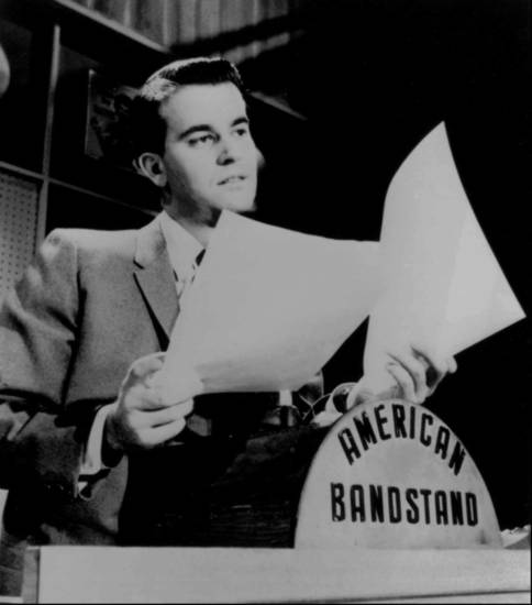 "ADV. FOR WKD. EDS., NOV. 4-7--FILE--Dick Clark looks over some papers during an ""American Bandstand"" show in Philadelphia in this undated photo. ""American Bandstand"" first aired as a local show in Philadelphia, gained popularity with host Dick Clark after he joined the program in 1956, and then went national in 1957. (AP Photo/File)"